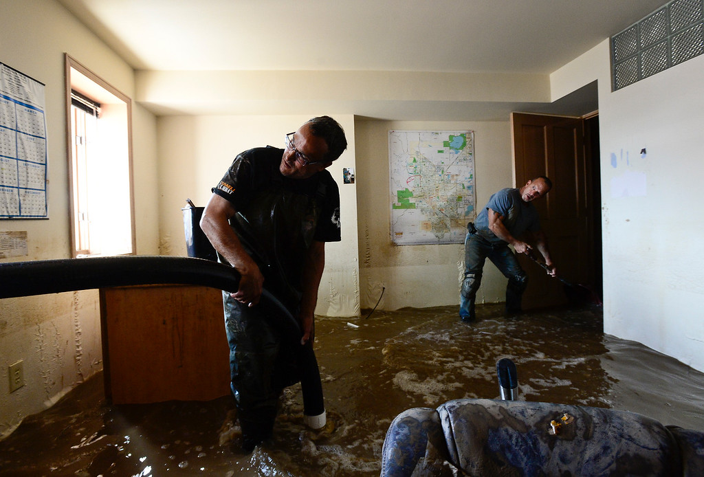 . Ray Hummer, left, pumps water out of his basement on Twin Peaks Circle with the help of Robert Pandolfi, Monday, Sept. 16, 2013, in Longmont. (Matthew Jonas/Times-Call)