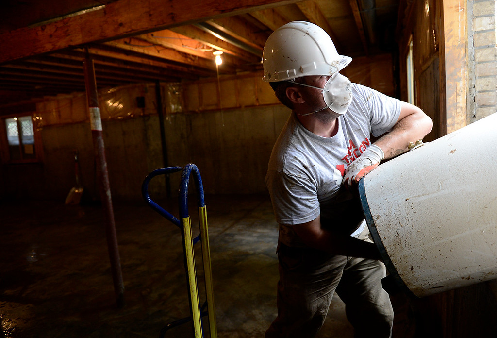 . Team Rubicon volunteer Nick Lascanic helps remove a water heater from a basement in The Greens neighborhood Thursday, Sept. 19, 2013. (Lewis Geyer/Times-Call)