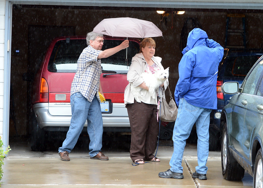 . Jay  Raymond puts an umbrella over his wife,  Margie, in the  McIntosh Lake area in Longmont, Colorado on September 15, 2013. They are discussing whether to leave the area or not. Cliff Grassmick / September 14, 2013