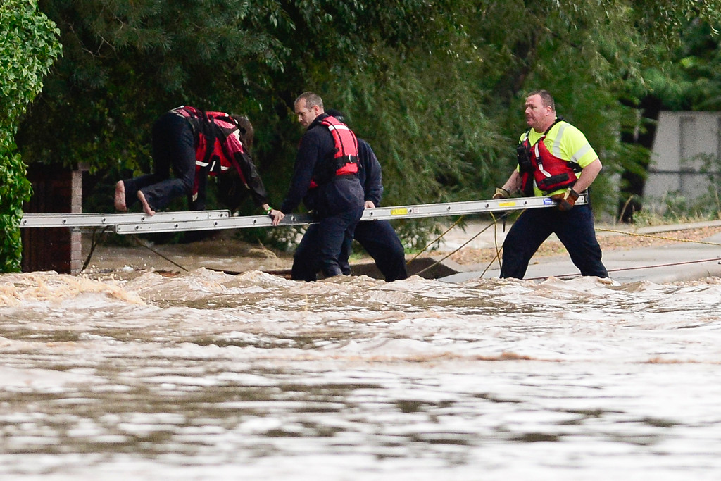 . Longmont Fire Department firefighters work to hold a ladder to rescue a woman who was stranded in high water near Pratt Street and Boston Avenue, Thursday, Sept. 12, 2013, in Longmont. (Matthew Jonas/Times-Call)