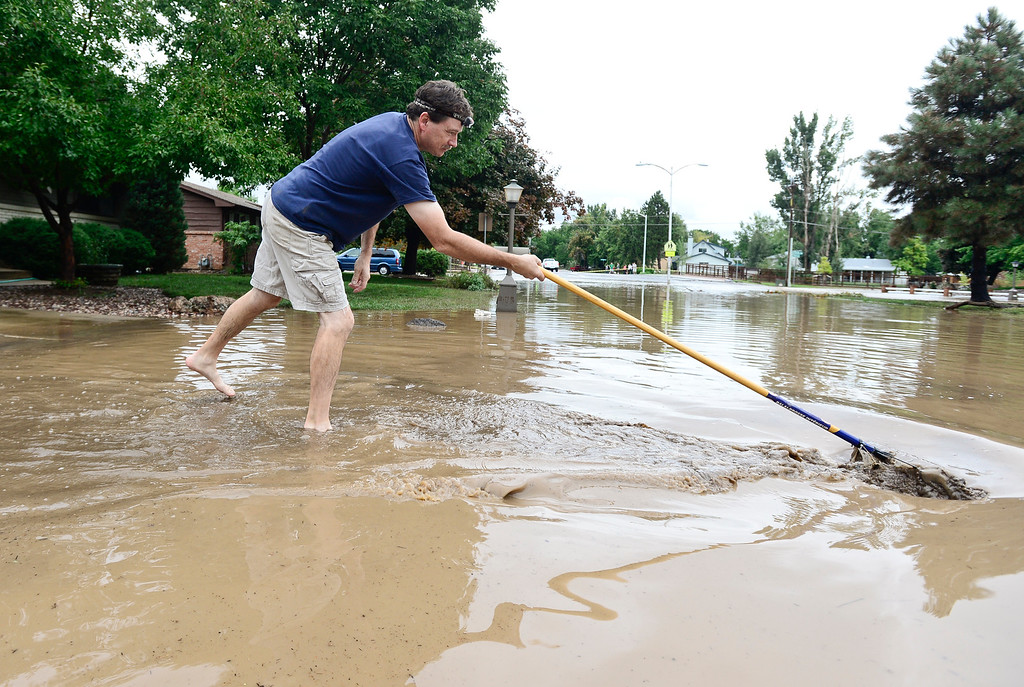 . Paul Douthitt, of Longmont, pushes mud and debris away from his driveway on South Pratt Parkway, Friday, Sept. 13, 2013, in Longmont. Douthitt said that they had 3 inches of water in their basement. (Matthew Jonas/Times-Call)