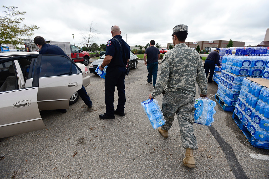 . Mountain View Fire Rescue firefighters and U.S. Army National Guardsmen load bottled water into vehicles, Monday, Sept. 16, 2013, in Del Camino. (Matthew Jonas/Times-Call)