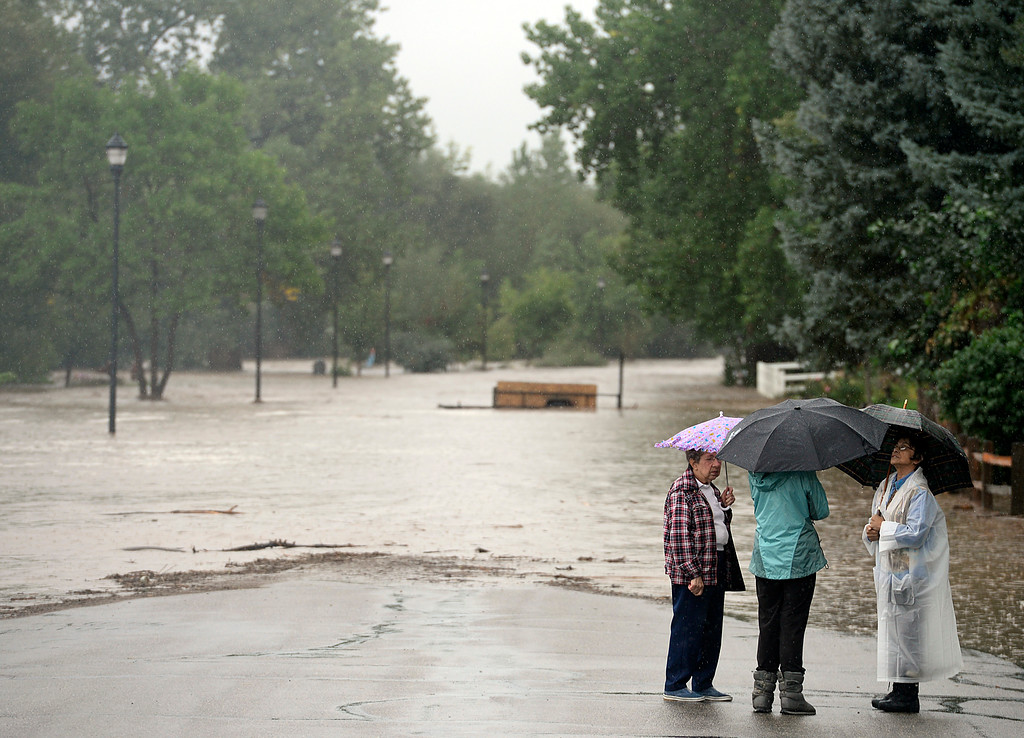 . Neighbors stand on a flooded Missouri Avenue, near Pike, 10 a.m. Thursday Sept. 12, 2013. (Lewis Geyer/Times-Call)