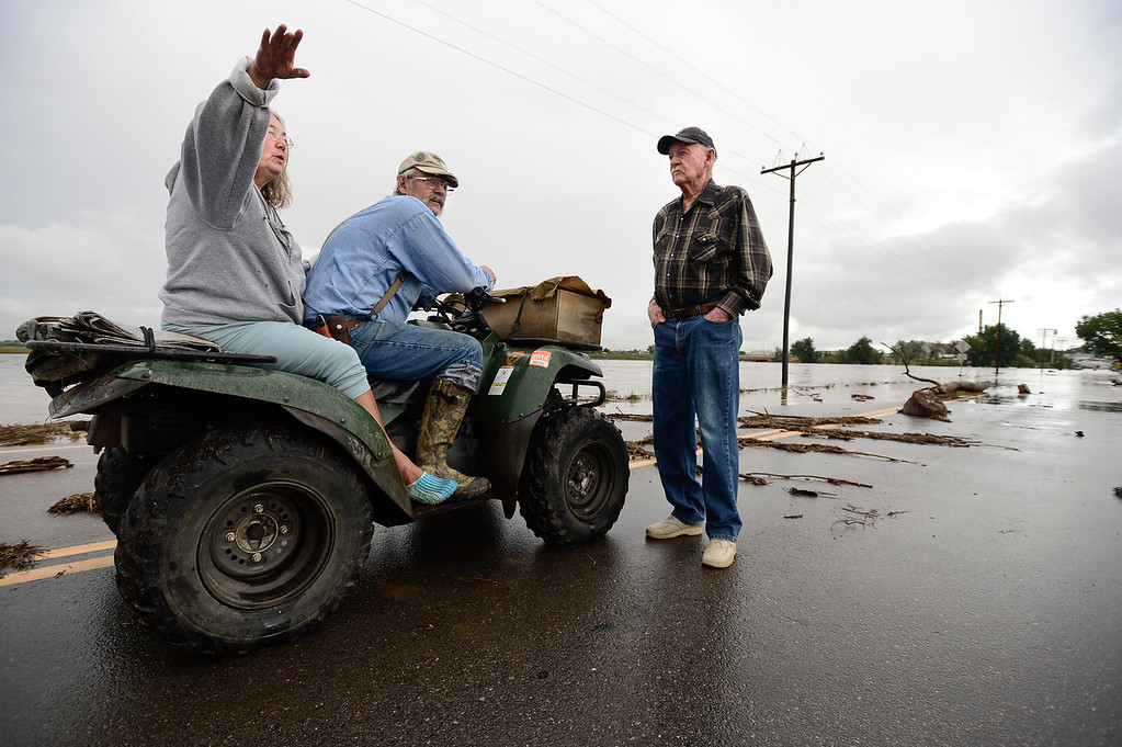 . From left: Julie and Mike Gunderson talk with Bob Rundle on a closed off section of North 119th Street, Friday, Sept. 13, 2013, in Longmont. The flood water from the St. Vrain River has closed many roads and made traveling from the South to the North difficult.  (Matthew Jonas/Times-Call)