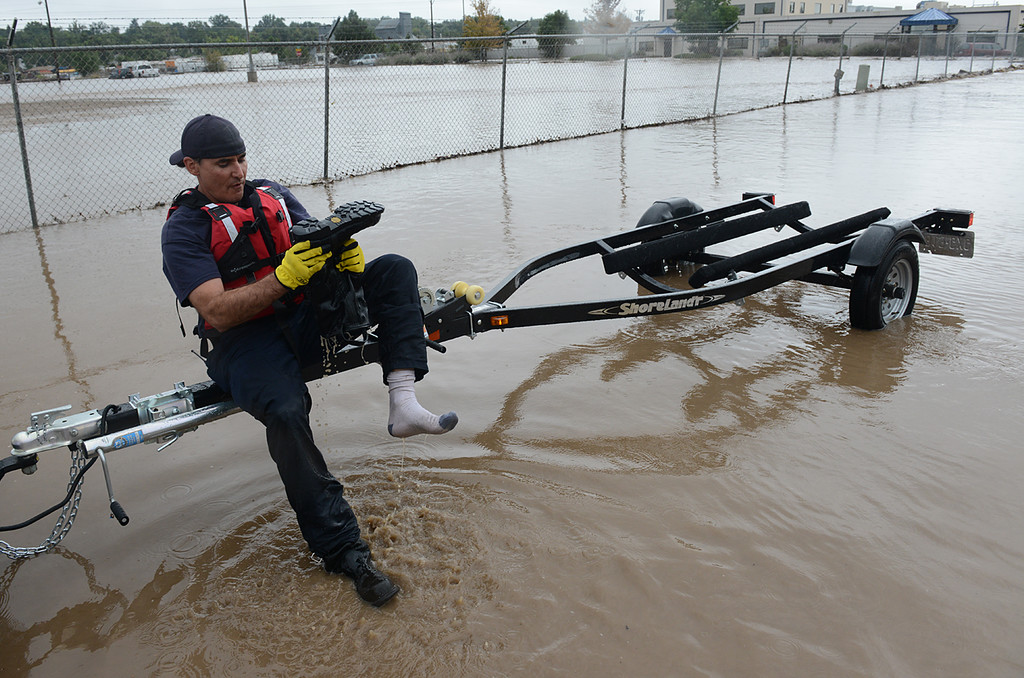. Longmont firefighter Todd Feaster empties water from his boot during a rescue operation on Boston Avenue in front of Left Hand Brewery Thursday Sept. 12, 2013. (Lewis Geyer/Times-Call)