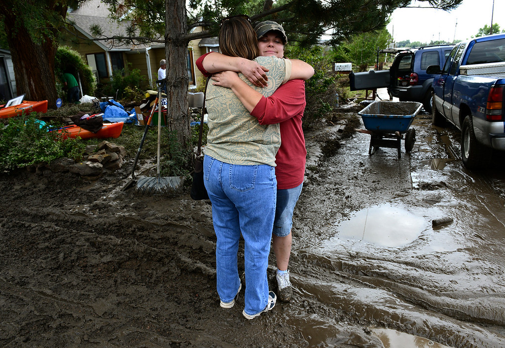 . Rachel Ferguson hugs a friend in front of the home at 108 Gay St., in the Bohn Park neighborhood, Saturday morning, Sept. 14, 2013. (Lewis Geyer/Times-Call)