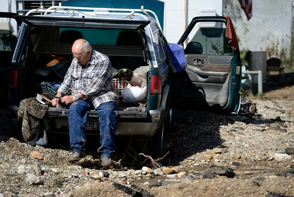 . Pete Ingino prepares his lunch Monday, Sept. 16, 2013 on the tailgate of his pickup after the business area had been reopened that morning. His pickup had sat in three feet of water Thursday while parked along Boston Avenue at S. Bowen Circle. (Lewis Geyer/Times-Call)