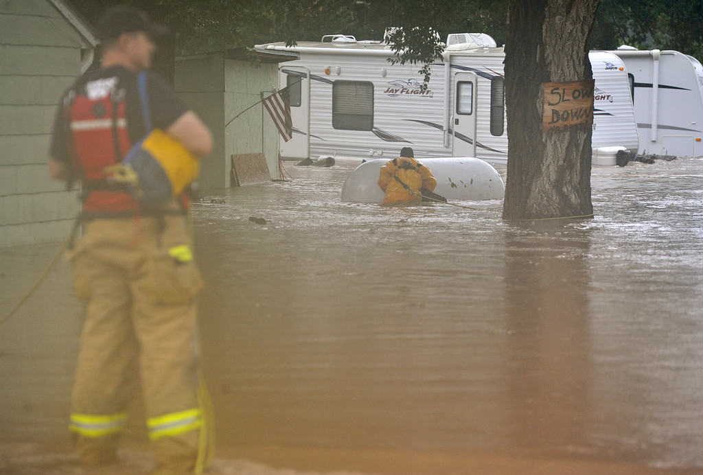 . Longmont Fire Department firefighters work to secure a propane tank to a tree in the 300 Block of Hover Street, Thursday, Sept. 12, 2013, in Longmont. (Matthew Jonas/Times-Call)