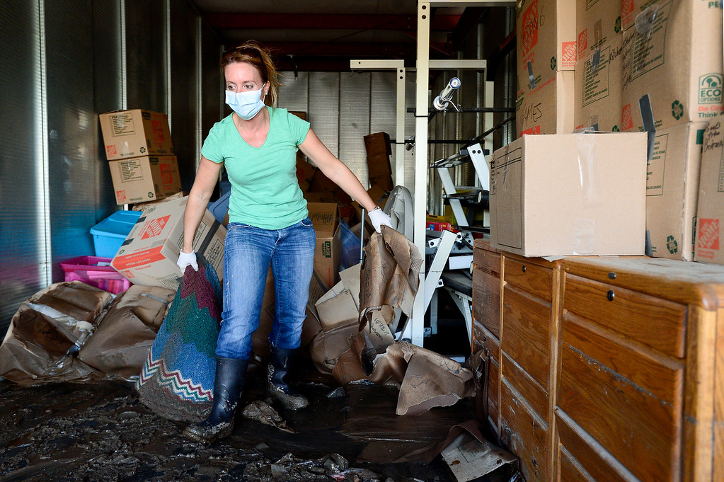 . Amber Genova, of Spring Gulch, a neighborhood near Lyons, removes flood damaged belongings while clearing out her storage unit, Monday, Sept. 23, 2013, at Storage West Self Storage in Longmont. The Genova\'s home near Lyons was not damaged by the flood. (Matthew Jonas/Times-Call)