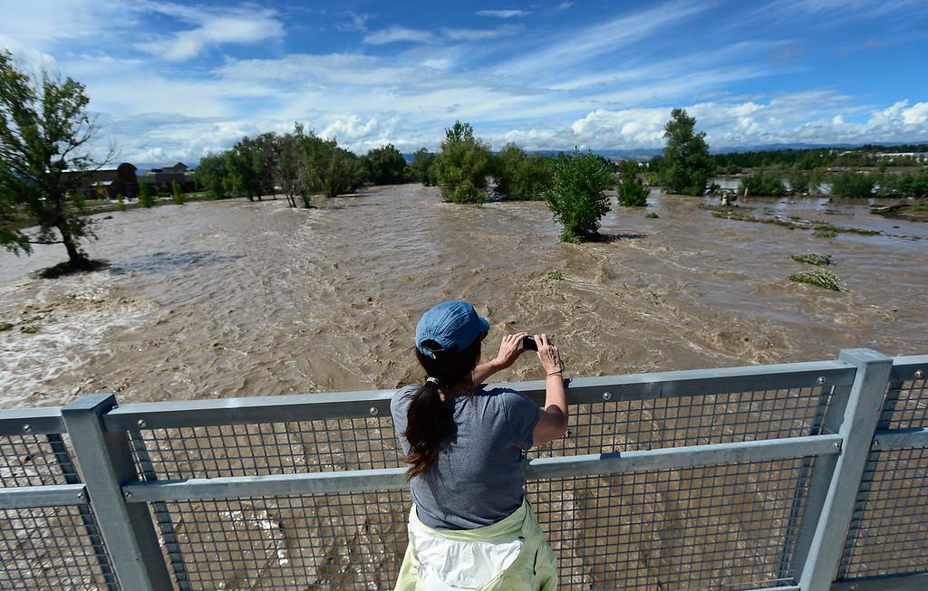. Kim Rapp, of Longmont, takes photos of the flooding St. Vrain River from the Martin Street bridge, Friday, Sept. 13, 2013, in Longmont. (Matthew Jonas/Times-Call)