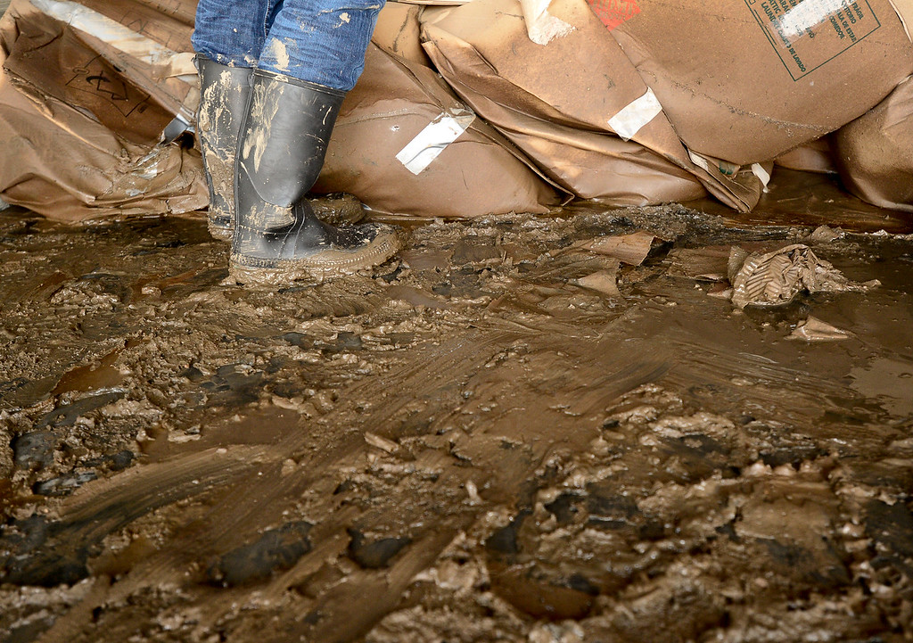 . Amber Genova, of Spring Gulch, stands in the mud in her storage unit while sorting belongings, Monday, Sept. 23, 2013, at Storage West Self Storage in Longmont. (Matthew Jonas/Times-Call)
