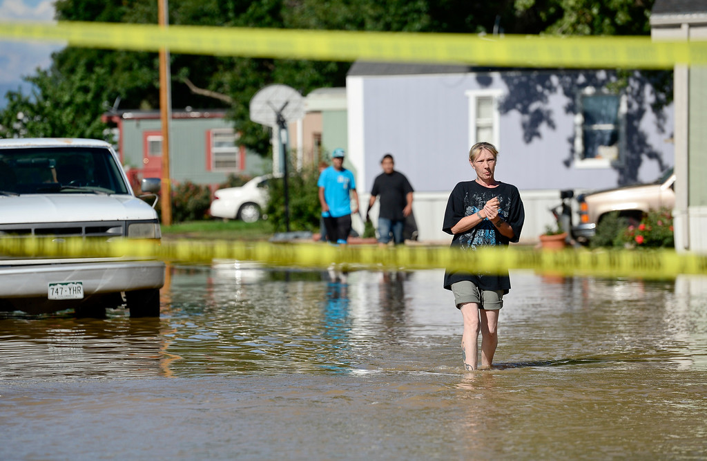 . Pam Benedetto, a resident of the River Valley Village mobile home park, right, walks through the flood water, Tuesday, Sept. 17, 2013, in Del Camino. Crews are expected to begin pumping water from the neighborhood today. (Matthew Jonas/Times-Call)