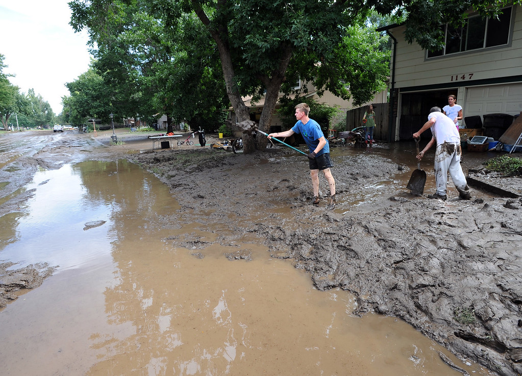 . Mark Swanson, right,  and Gabe Anderson, shovel out the mud from this home on Lefthand Drive in Longmont, Colorado, on September 14, 2013. Cliff Grassmick / September 14, 2013