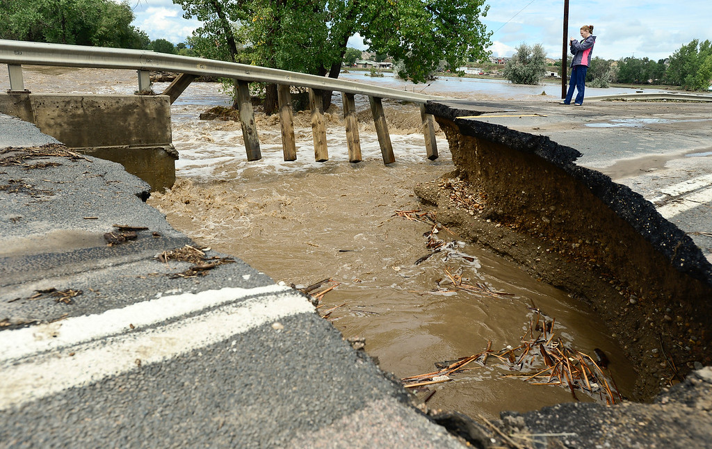 . A woman takes photos of a guard rail and flood damage on County Line Road, Friday, Sept. 13, 2013, near Longmont. (Matthew Jonas/Times-Call)