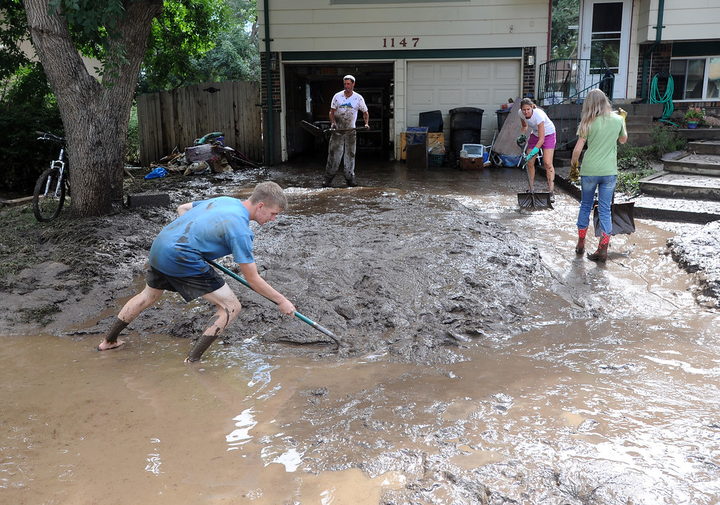 . Gabe Anderson, left, Mark Swanson, top, Stefani Anderson, and Savana Anderson, work as a family to clean the mud out of their yard on Lefthand Drive in Longmont Colorado on September 14, 2013. Cliff Grassmick / September 14, 2013