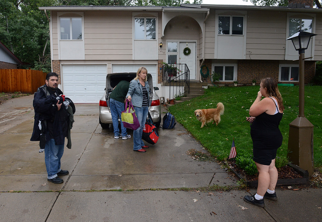 . S. Bowen Street neighbors Sarah Johnson, center, and Jamie Martin, right, talk as they evacuate 9:30 a.m. Thursday Sept. 12, 2013. (Lewis Geyer/Times-Call)