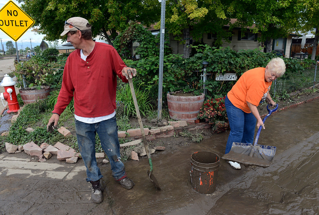 . Gabriel Brown helps his mother Helen M. Brown remove mud from the street in front of her home on Grant Street at First Avenue, in the Bohn Park neighborhood, Saturday morning, Sept. 14, 2013. (Lewis Geyer/Times-Call)